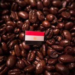 a Egypt flag placed over roasted coffee beans