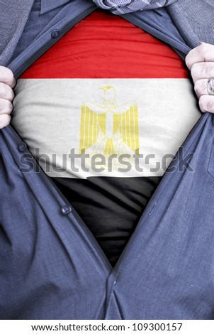A Egyptian businessman rips open his shirt and shows how patriotic he is by revealing his countries flag beneath printed on a t-shirt