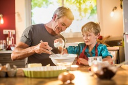 A eight years old blond boy is cooking  with his father in a luminous kitchen. They are sitting at a wooden table the dad is mixing the preparation while his son is adding ingredients.Shot with flare