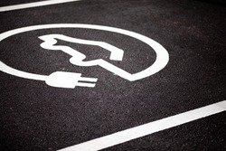A Electric car parking bay, with a EV/Logo design on the floor - Showing this is for plug-in/electric cars only. Nice detail on the road markings and texture of the road.