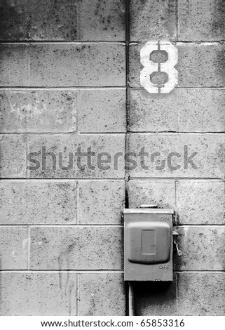 A electrical junction box against a concrete block wall and the number eight.
