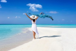 A elegant tourist woman in white summer dress walks on a tropical beach with a waving scarf in her hand