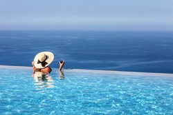 A elegant woman with hat and wine glass in her hand stands at the edge of an infinity pool and enjoys the view over the blue sea