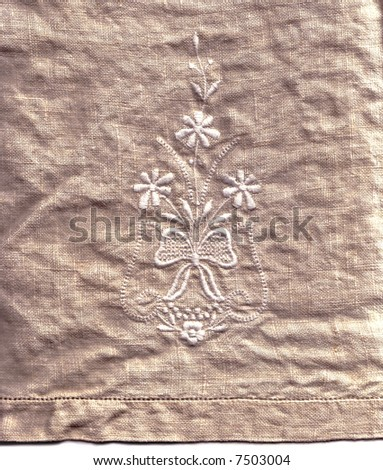 A embroidered linen hand-towel, suitable for a background texture.