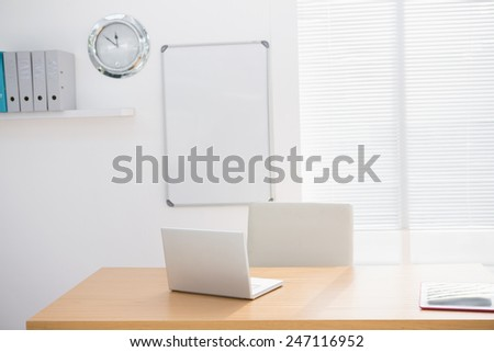 A empty lighted office with a laptop