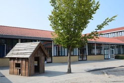 A empty school yard with a playhouse and tree