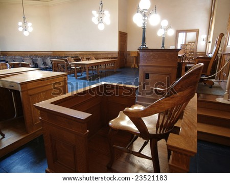 A empty witness chair inside a classic American courtroom.