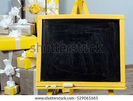 a empty yellow tripod on wooden floor with grey wall and heap of yellow and grey christmas gift box