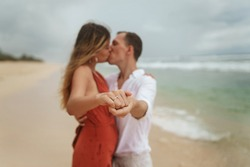 A engagement ring on the finger of a young beautiful blonde girl in a red dress and a handsome young guy in white clothes kisses on the sandy shore of the ocean. Wedding couple cuddling on the beach