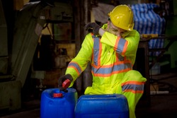 A Engineer industry wearing safety uniform ,black gloves ,gas mask feel suffocate when under checking chemical tank in industry factory work.
