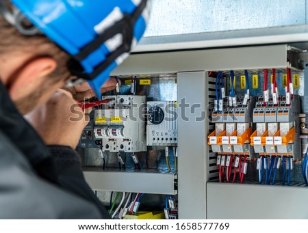 A engineer repairing electrical installation stock photo