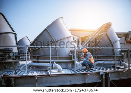 A engineer under checking the industry cooling tower air conditioner is water cooling tower air chiller HVAC of large industrial building to control air system.