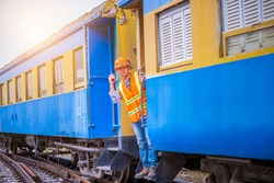 A engineer under inspection and checking construction process railway work on rail train station by radio communication ,Engineer wearing safety uniform and safety helmet in work.