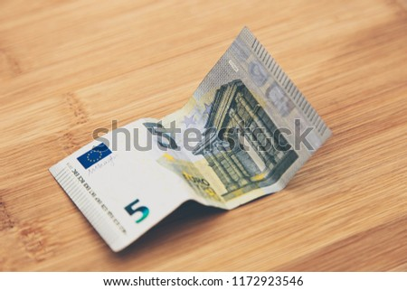 A 5 euro banknote on a wooden table top.  This image can be used as a money background