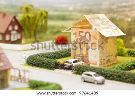 a euro bill house in a green neighborhood scenery
