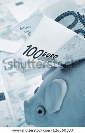 a 100 euro bill in a piggy bank