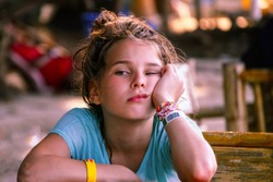 A European-looking girl with a face expressing boredom and anticipation. Asian cafe, travel with children, local cuisine. The background is blurred.
