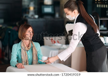 A European-looking waiter in a medical mask serves coffee