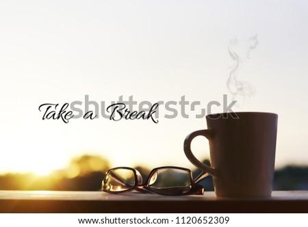A eyewear glasses and mug with sunset background. Wording