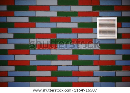A facade made of colorful clinker with a ventilation grille in the wall.