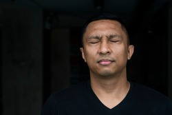 A face of an Asian Indonesian man forcing his eyes closed as if he 's ridden with guilty conscience. The portrait is on black and the model wears black t-shirt