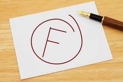 A failing grade, A white card with text of  F and a fountain pen on a wooden desk