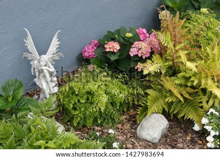 A fairy sculpture sits in a garden of hydrangeas, ferns, and impatiens