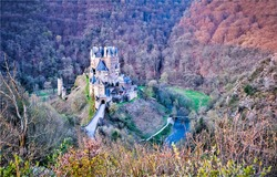 A fairytale castle in the mountain forests. Castle in forest. Forest castle panorama. Fairy tale castle in forest