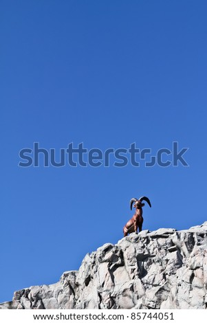 A fake capricorn on fake rock next to a ride in an amusement park in Vienna