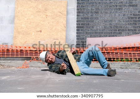 A fallen and injured construction worker in a hard hat laying on the ground at a construction work site
