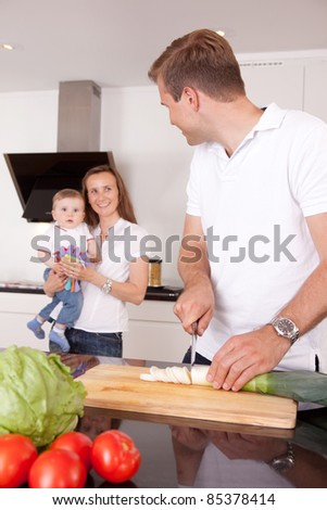 A family at home in the kitchen making a meal together, shallow depth of field, critical focus on father