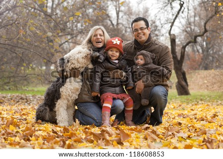 A family enjoying time together in a park during the Autumn season.