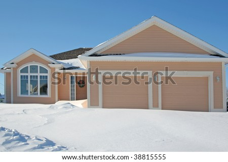A family home with a two car garage surrounded by snow.