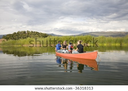 A family in a canoe on the pond.