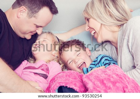 A family in bed laughing together.