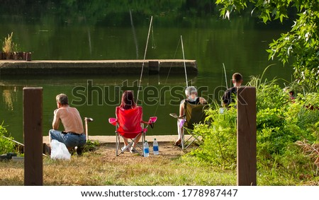 A family is having fun time fishing altogether in Mallows bay of the Potomac river at a lovely afternoon. Each have fishing rods and they line up by the river having family time.