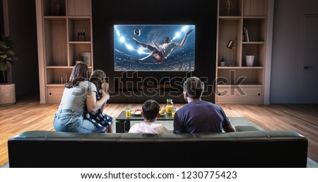 A family is watching a soccer moment on the TV and celebrating a goal, sitting on the couch in the living room. The living room is made in 3D. Foto stock ©