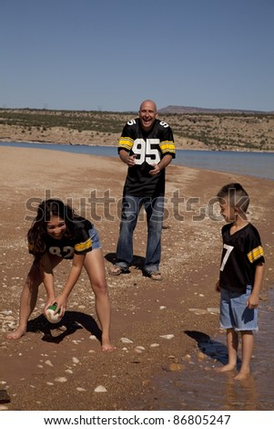 a family laughing and having fun playing football.