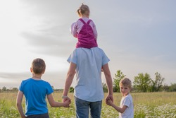 A family of dad, of two sons and daughter walk in a green meadow. Daughter sits on dad's shoulders. Hold hands. International Children Day.