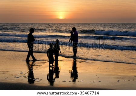 A family of five at the beach at sunrise.