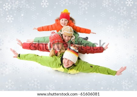 A family of four in warm clothing lying on each other with outstretched arms - stock photo
