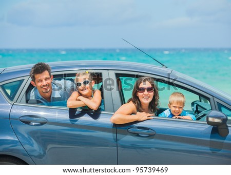 A family of four, mother, father, son and daughter driving in a car on a sunny day in hot location, backround sea