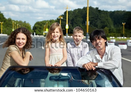 A family of four, parents stand on the sides of the windshield at the gig, daughter - on the front seat, son - on the back.