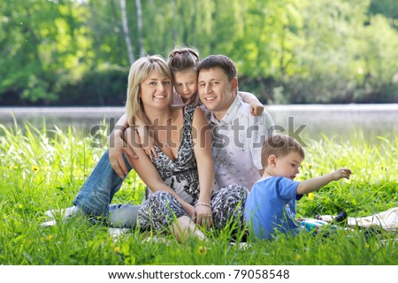 A family of four persons - father, mother, son and daughter, have a rest on the nature on the bank of the river