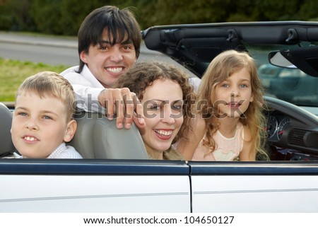 A family of four sits in a cabriolet, three of them smile and look into the camera, the son looks the other way