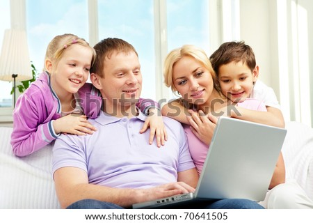 A family of four sitting on sofa and looking at laptop screen