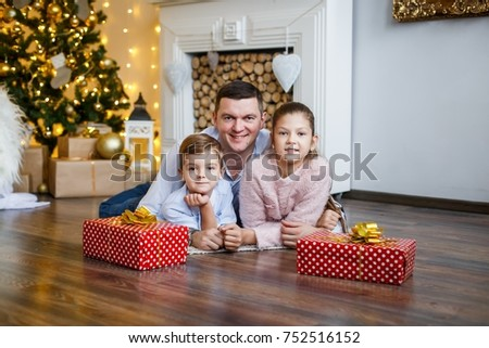 A family of three  in front of the fur-tree and fireplace with candles and gifts. New year's eve. Christmas eve. Cozy holiday at the fir-tree with lights and gold decor. #752516152