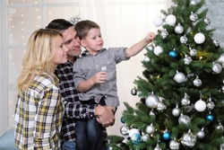 A family of three people exchanging New Year's gifts sitting on the windowsill at the window with a Christmas tree
