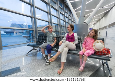 A family of three sitting in a recreation area at the airport #136151768