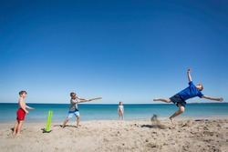 A family playing the traditional Aussie game of cricket on the beach.